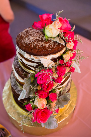wedding ceremony: Custom wedding cake at reception with pink flowers and different fillings between chocolate.