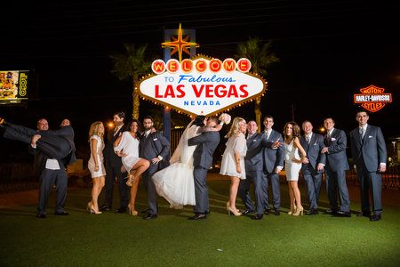 LAS VEGAS, NV - DECEMBER 12, 2014: Wedding party with the bride and groom in front of the Las Vegas sign in Nevada at night. Редакционное