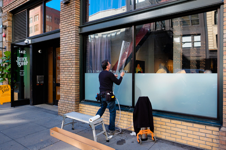 SAN FRANCISCO, CA - DECEMBER 11, 2015: Windown decal worker placing a sticker on the window of a coffee shop in San Francisco. Redactioneel