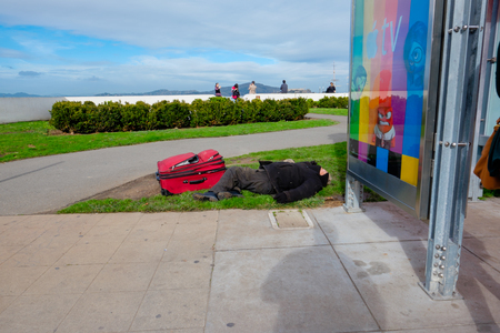 drug use: SAN FRANCISCO, CA - DECEMBER 12, 2015: Homeless man sleeping with luggage at a bus stop in San Francisco.