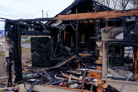 homeowners insurance: House burned almost completely in a major fire leaving only the damaged remains of this home. Stock Photo