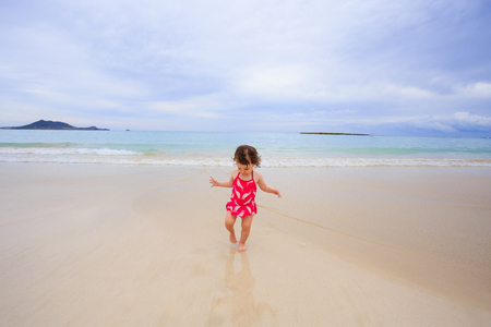 one year: One year old girl playing in the waves in her swimsuit at Kailua Bay Beach in Oahu Hawaii.