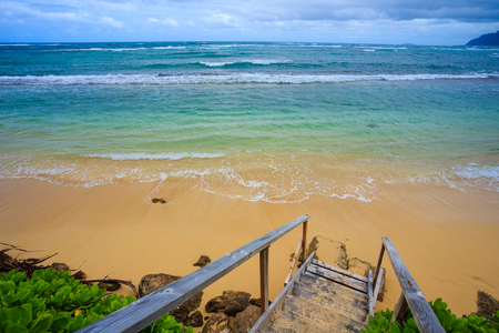 north shore: Stairs lead down to an amazing beach on the North Shore of Oahu Hawaii where guests can rent houses and stay in a tropical paradise for vacation and relaxation. Stock Photo
