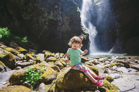 national forest: Young girl about 1.5 years old posing for a portrait under a tall waterfall in the Umpqua National Forest in Oregon.