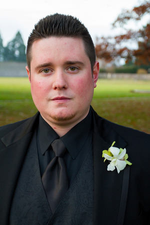 tux: Groom posing for a portrait outdoors on his wedding day in Oregon, wearing a black tux.