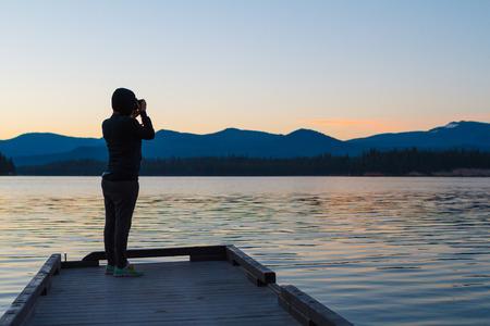 デジタル一眼レフのデジタル カメラで写真家夕暮れの湖の写真を撮影します。 写真素材
