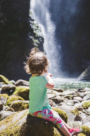 oregon cascades: Young girl about 1.5 years old posing for a portrait under a tall waterfall in the Umpqua National Forest in Oregon.