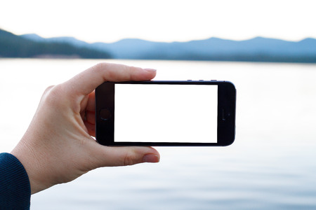 Mobile photography has gained traction in recent years and this image of a smartphone being used at a lake in Oregon can easily have an image added to the white phone screen.