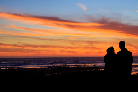 anniversary beach: Couple from the back at sunset on a beach in Oregon.