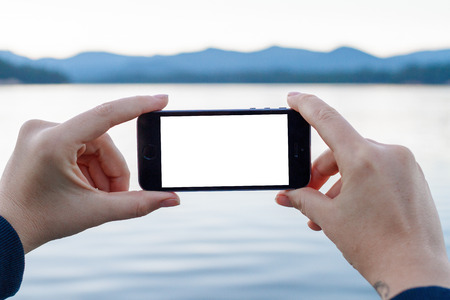 traction: Mobile photography has gained traction in recent years and this image of a smartphone being used at a lake in Oregon can easily have an image added to the white phone screen.