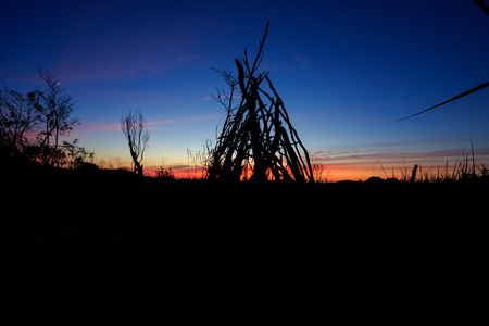 tipi: Oregon beach with a stick tipi at sunset along the coastline and a colorful sky.