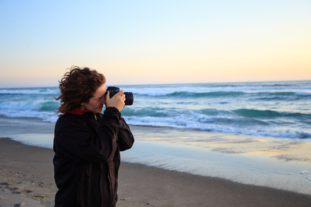 ocean and sea: Sunset photos being shot by a woman with a camera on the beach at dusk.