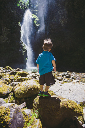 three year old: Three year old boy standing at the base of a large waterfall in the Umpqua National Forest in Oregon.