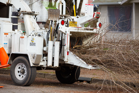 wood cutter: SPRINGFIELD, OR - FEBRUARY 16, 2016: Wood chipper trailer attached to the back of a utility work truck.