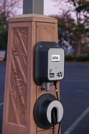 electric vehicle: SAN DIEGO, CA - JANUARY 29, 2014: Solar powered electric vehicle car charging station in a public parking lot in California.