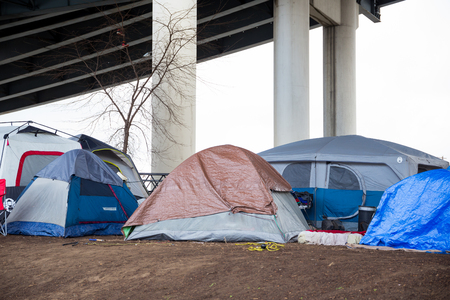 PORTLAND, OR - FEBRUARY 27, 2016: Homeless camps with tents and tarp shelter under a bridge in downtown Portland Oregon. Sajtókép