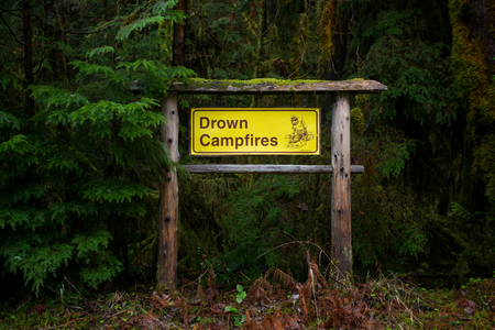 drown: MCKENZIE BRIDGE, OR - MARCH 5, 2016: National Forest Service sign reminding campers to drown campfires while camping.