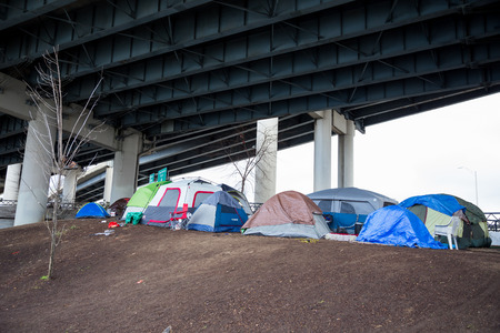 PORTLAND, OR - FEBRUARY 27, 2016: Homeless camps with tents and tarp shelter under a bridge in downtown Portland Oregon. Publikacyjne