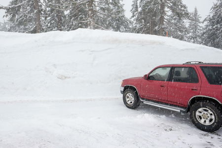 crater lake: CRATER LAKE, OR - MARCH 8, 2016: Red Toyota 4Runner SUV parked next to a snowpack of more than 100 inches at Crater Lake after a Winter of record-setting snowfall.