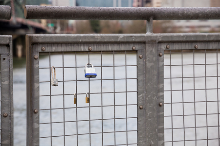 recreate: PORTLAND, OR - FEBRUARY 27, 2016: Locks are locked to a fence on a bridge across from downtown Portland Oregon in an attempt to recreate the historic Lovers Bridge in Paris France.