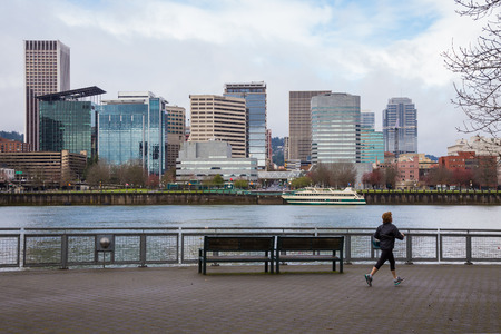willamette: PORTLAND, OR - FEBRUARY 27, 2016: The city skyline of Portland across the Willamette River as a runner jogs by on the SE waterfront path downtown.