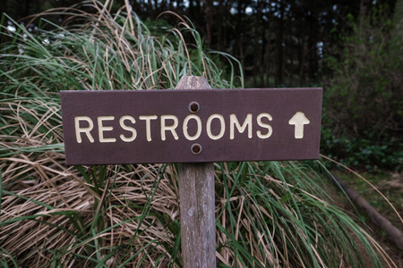 Restrooms sign with an arrow points toward a nature trail that leads to the bathroom at a campground in Oregon.