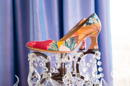 stilleto: Wedding day shoes for the bride on a custom chandelier at a hotel.