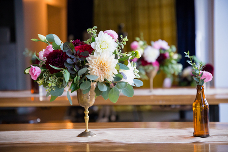 centerpiece: Wedding flowers on reception tables setup by a florist using vintage antique bottles.