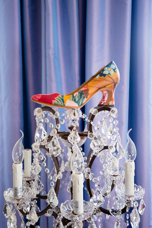 stilletto: Wedding day shoes for the bride on a custom chandelier at a hotel.