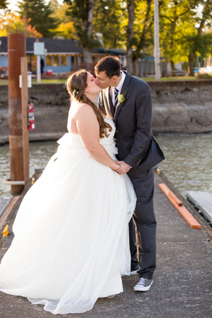 relational: Portrait of a bride and groom on their wedding day at a yacht club marina in Oregon.