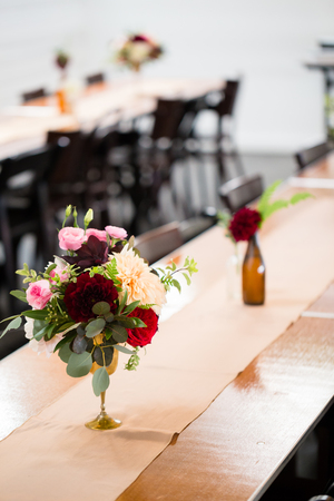 Wedding flowers on reception tables setup by a florist using vintage antique bottles. photo & Wedding Flowers On Reception Tables Setup By A Florist Using.. Stock ...