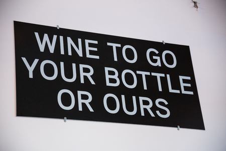 ours: Winery that sells growler fills of wine has a sign that says wine to go your bottle or ours. Stock Photo