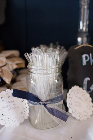 favors: Party favors for the guests of this wedding are custom made blown glass straws.