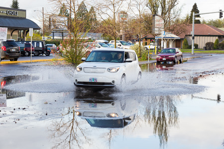 torrential: EUGENE, OR - MARCH 20, 2016: Automobile driving through a large puddle on the University of Oregon campus after torrential rainstorms moved through Eugene. Editorial
