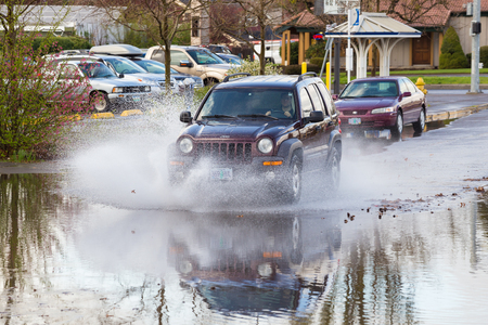 EUGENE, OR - MARCH 20, 2016: Automobile driving through a large puddle on the University of Oregon campus after torrential rainstorms moved through Eugene. Editorial