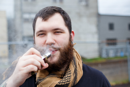 mod: Urban lifestyle portrait of a man vaping in an urban environment with a custom vape mod device.