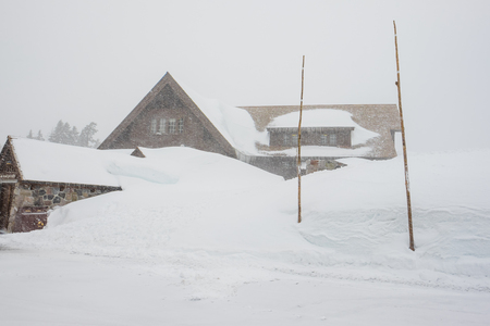 crater lake: Crater Lake Lodge is barely visible in extreme blizzard whiteout conditions during the Winter of 2016. Stock Photo