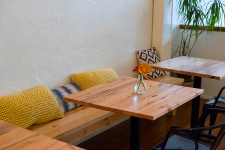 Bench Seating At A Coffee Shop Restaurant With Small Cafe Tables And  Pillows. Stock Photo