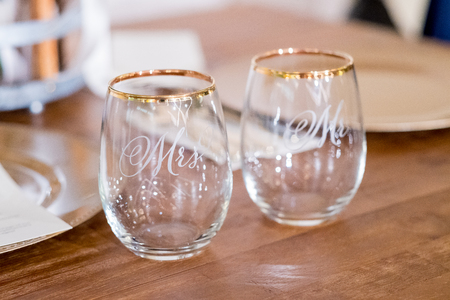 Mr and Mrs wedding wine glasses at an elegant indoor reception.