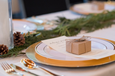 candlelit: Wedding reception tables with seating, plates, and candles at a winter wedding in Oregon. Stock Photo