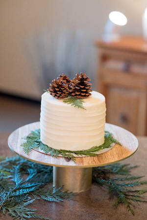 topper: White wedding cake at a reception with a pinecone topper. Stock Photo