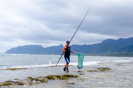 LAIE, HAWAII - FEBRUARY 24, 2017: Fisherman Jameson Humalon competes in a saltwater fishing tournament on Oahu targeting bonefish on the windward side of the island. Editorial