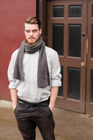 Hipster posing outdoors for the camera with a fashion forward style and a modern man appearance. Banco de Imagens