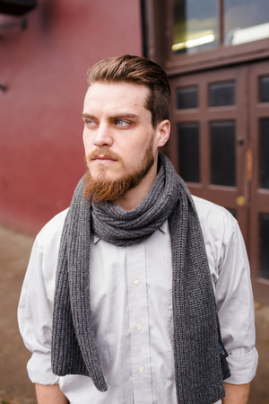 Hipster posing outdoors for the camera with a fashion forward style and a modern man appearance. Stock Photo