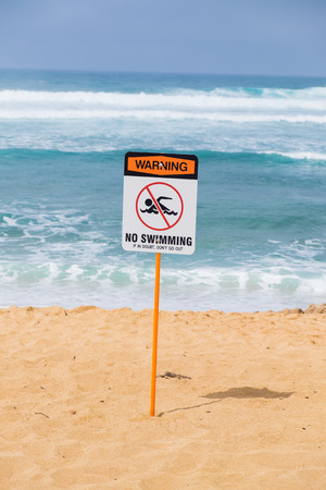 no swimming sign: Storng current no swimming sign in front of a popular surf spot at Haleiwa Beach on Oahu Hawaii.