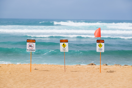 Storng current no swimming sign in front of a popular surf spot at Haleiwa Beach on Oahu Hawaii.