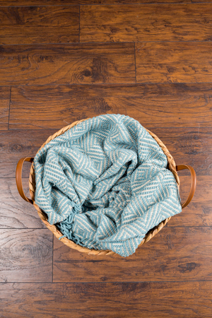 Basket with a blanket inside awaiting a newborn baby during a studio photo session by a professional photographer. Фото со стока