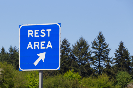 Blue rest area sign points to a highway exit where drivers can relax and rest during their travel.