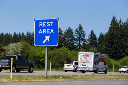 INTERSTATE 5, OR - MAY 7, 2015: Blue rest area sign point to a public exit off the highway with vehicles passing by in the background.