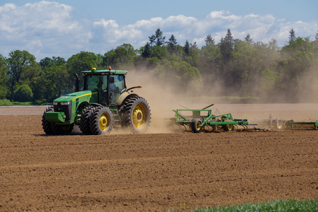 grower: ALBANY, OR - MAY 7, 2015: John Deere commercial tractor plowing a field at a farm near Albany Oregon getting ready to plant seeds for food to grow. Editorial